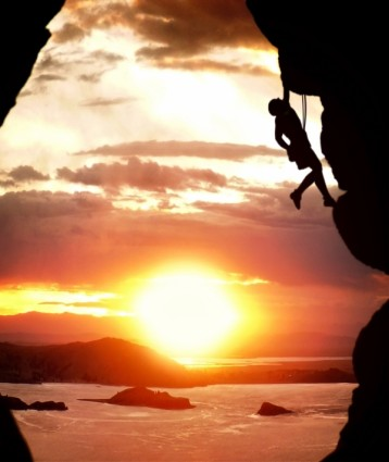 Free Climber Rising At Sundown